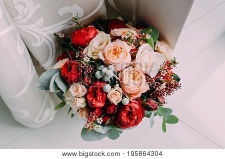 Beautiful wedding bouquet of red flowers, pink flowers and greenery stand on the light background next to the window. View from above