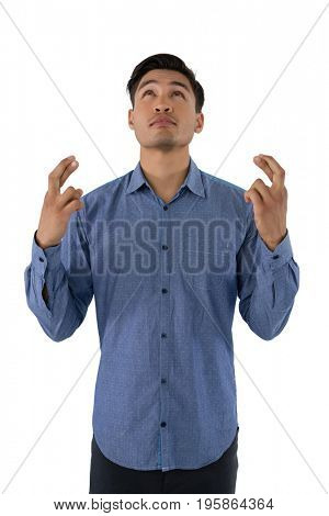 Businessman with crossed fingers looking up while standing against white background