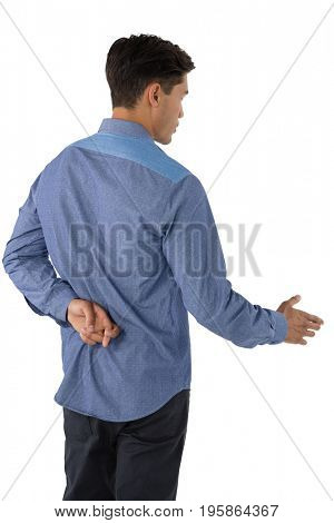 Rear view of businessman extending arm for handshake with fingers crossed against white background