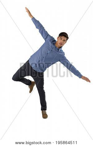 Full length of businessman with arms outstretched balancing while standing against white background