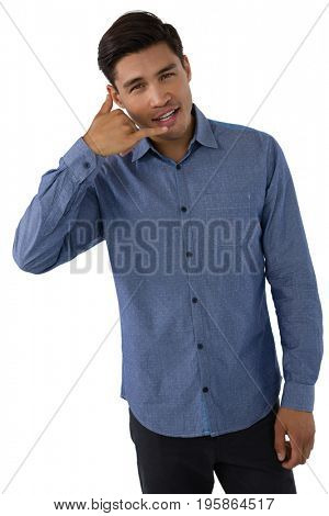 Portrait of businessman gesturing call hand sign against white background