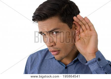 Close up portrait of businessman cupping ears while standing against white background