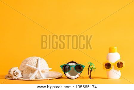Summer hat, coconut and sunblock wearing sunglasses on a yellow background