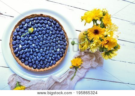 Cake with berries. Pie with blueberries at white rustic table with summer flower. Blueberry. Morning and breakfast concept.