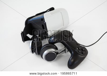 Close-up of joystick, virtual reality headset and headphones on white background