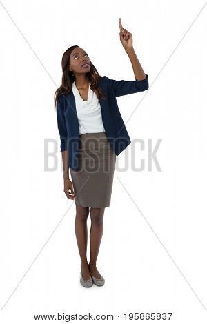 Full length of businesswoman pointing upwards while standing against white background