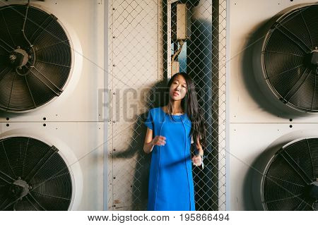 Young Beautiful Asian Woman, On A Background Of Industrial Air Conditioning System Fans