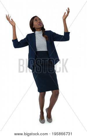 Businesswoman gesturing while tiptoeing against white background