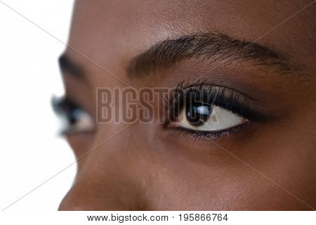 Close up of woman eyes looking away against white background