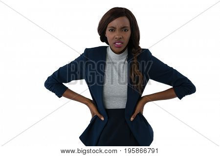 Portrait of irritated businesswoman with hands on hip standing against white background