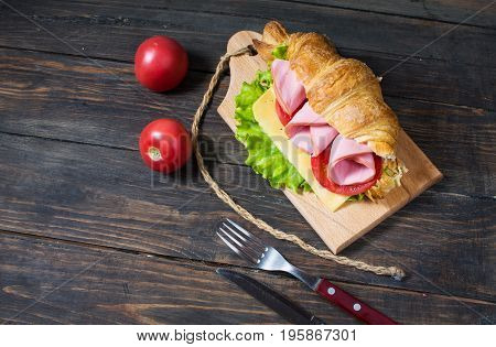 Light and hearty spring breakfast. Croissant with ham, cheese, fresh tomatoes on a wood stone table.