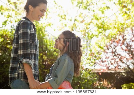 Smiling mother looking at daughter while holding her friends at backyard on sunny day