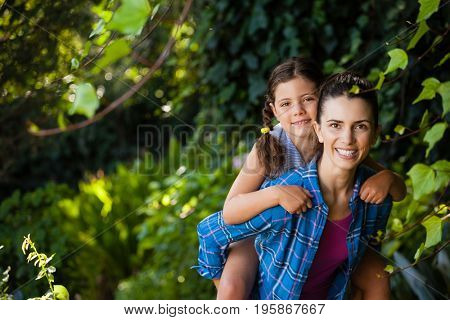 Portrait of cheerful woman piggybacking daughter against trees in backyard