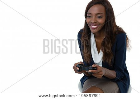 Smiling businesswoman playing video game while sitting on stool against white background