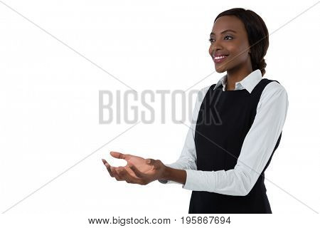 Smiling woman gesturing while standing against white background