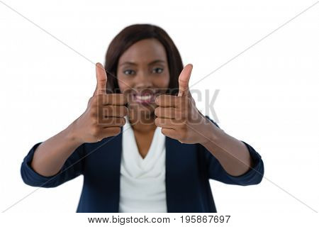 Woman showing thumbs up gesture against white background