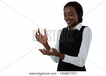 Happy woman gesturing while standing against white background