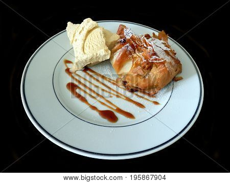 Apple in filo pastry dusted with icing sugar and served with vanilla ice cream and caramel sauce
