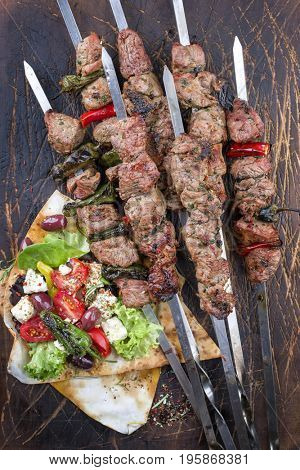 Traditional Shashlik with Salad and Yufka Bread as top view on an old burnt cutting board