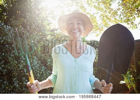Back lit portrait of smiling senior woman holding garden fork and shovel at backyard