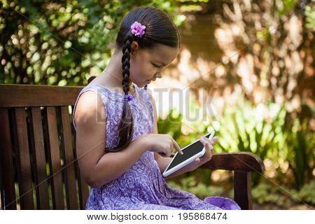 Girl using digital tablet while sitting on wooden bench at backyard