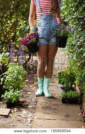 Low section of woman girl with potted plants on footpath in backyard
