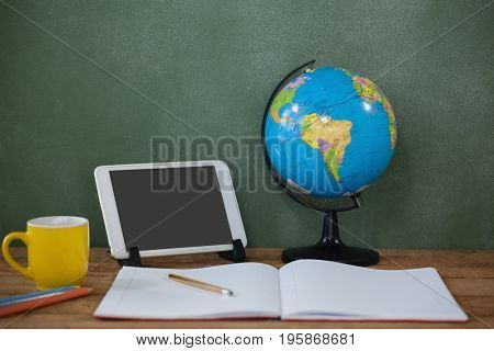 Close-up of digital tablet and globe on table in classroom at school
