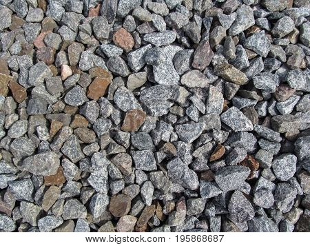 Background of large gray-red-brown rubble. Crushed gravel close-up - top view