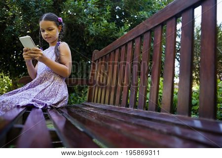 Surface level of girl sitting on wooden bench while using mobile phone at backyard