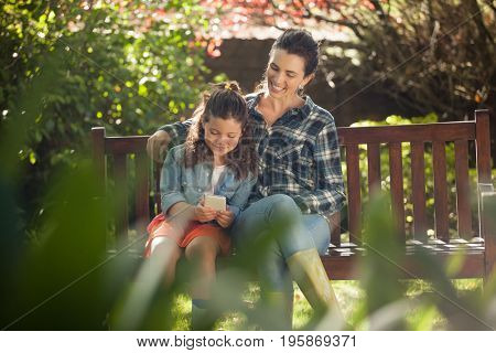 Smiling woman sitting with arm around daughter using mobile phone on wooden bench at backyard