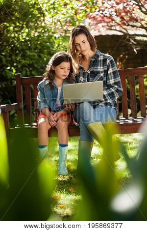 Girl sitting by mother using laptop on wooden bench at backyard