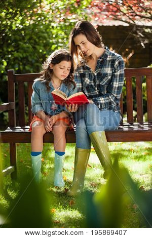 Mother reading book to daughter while sitting on wooden bench at garden
