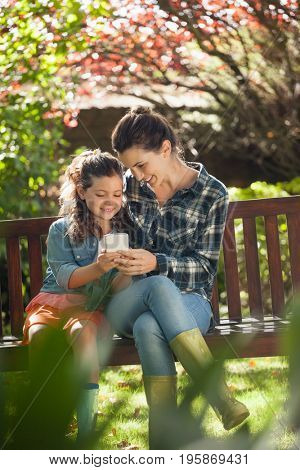 Smiling girl and mother using mobile phone while sitting on wooden bench at backyard