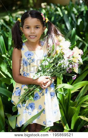 Portrait of smiling girl holding flowers bouquet standing amidst plants in backyard