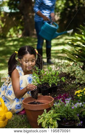 Girl planting in pot while grandmother watering plants at backyard