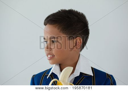 Thoughtful schoolboy having banana against white background