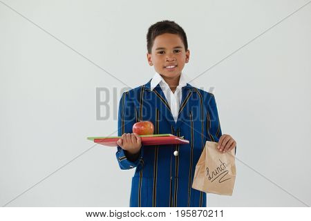 Portrait of schoolboy holding apple, books and disposable lunch bag against white background