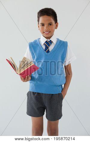 Portrait of schoolboy standing in front of chalkboard in classroom at school