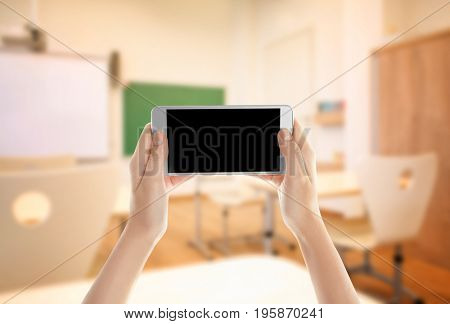 Teacher holding smartphone with blank screen and classroom on background. Concept of school and modern technology