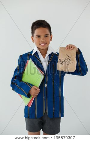Portrait of schoolboy holding books and disposable lunch bag against white background