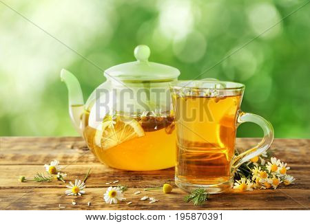 Hot chamomile tea in cup and pot with flowers on wooden table outdoor