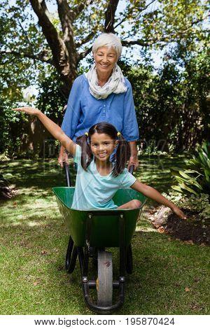 Smiling senior woman pushing wheelbarrow with granddaughter at backyard