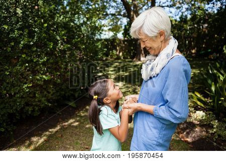Side view of smiling grandmother and granddaughter standing while holding hands at backyard