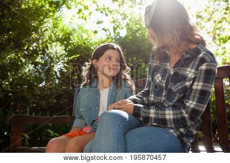 Girl sitting with mother on wooden bench against trees at backyard during sunny day
