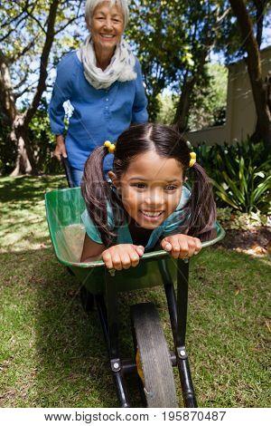 Cheerful senior woman pushing wheelbarrow with granddaughter at backyard