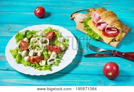Light and hearty spring breakfast. Croissant with ham, cheese, fresh tomatoes and salad with Mozzarella on a wood table