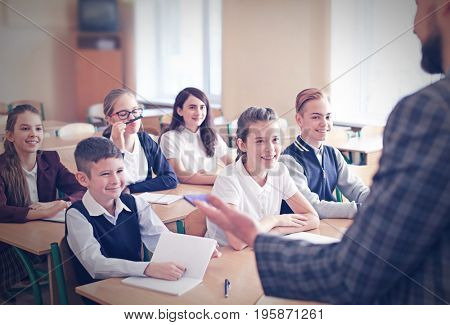 Children listening teacher in classroom at school