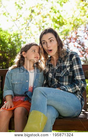 Girl whispering in ears of smiling surprised mother while sitting on bench at backyard