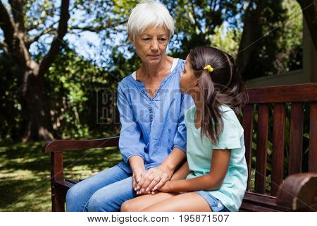 Grandmother and granddaughter holding hands while sitting on bench at backyard