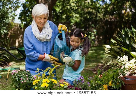 Smiling grandmother and granddaughter watering plants in backyard